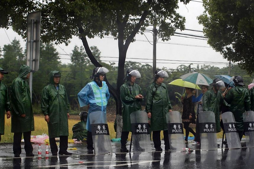 Riot police stand by the side of the road at the entrance of Yuhang town after a night of riots west of Hangzhou, Zhejiang province on May 11, 2014. -- PHOTO: REUTERS