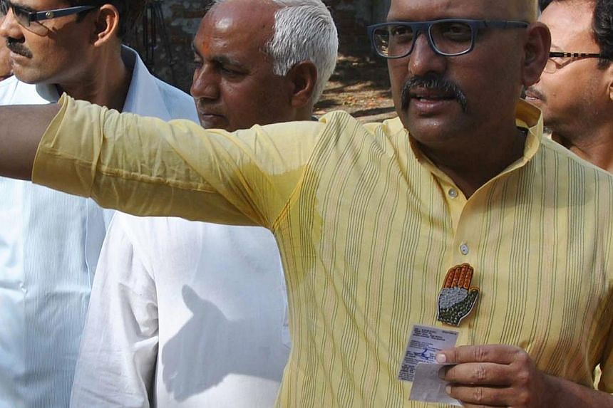 India's Congress party candidate Ajay Rai is pictured wearing a lapel pin bearing his party's logo as he waits in line to vote at the Ramakant Nagar polling station in Varanasi on May 12, 2014. -- PHOTO: AFP