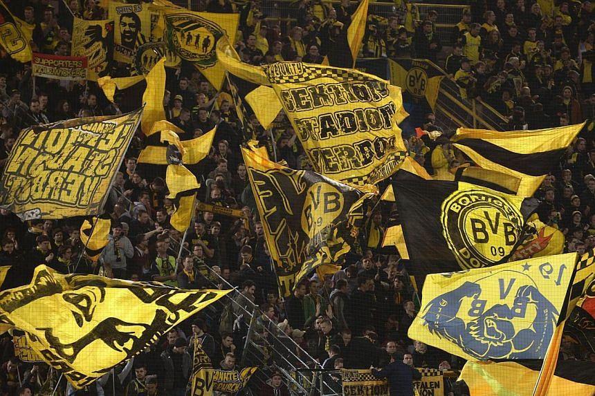 Dortmund's fans cheer prior to the last 16 second-leg UEFA Champions League football match Borussia Dortmund vs Zenit St Petersburg in Dortmund, western Germany on March 19, 2014. Borussia Dortmund were the only European club to average more than 80,