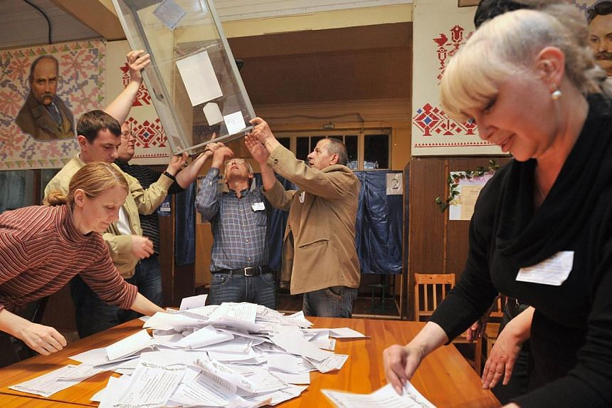 A member of an election commission counts ballot papers as the others empty a ballot box at a polling station in the eastern Ukrainian city of Donetsk on May 11, 2014. -- PHOTO: AFP