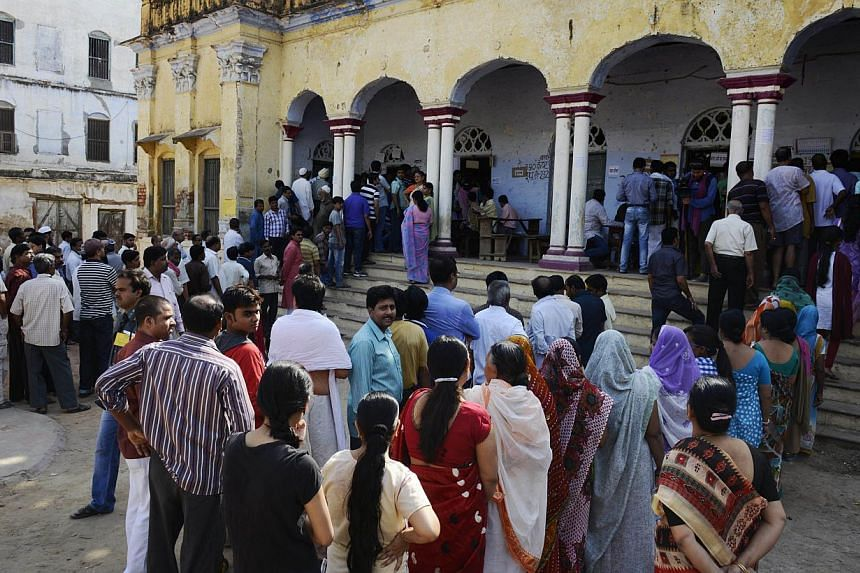 Residents line up to vote at a local polling station set up at a school in Varanasi on May 12, 2014. A record 551 million voters cast their ballots in India's general election which also saw the highest ever turnout rate of 66.38 per cent, organ