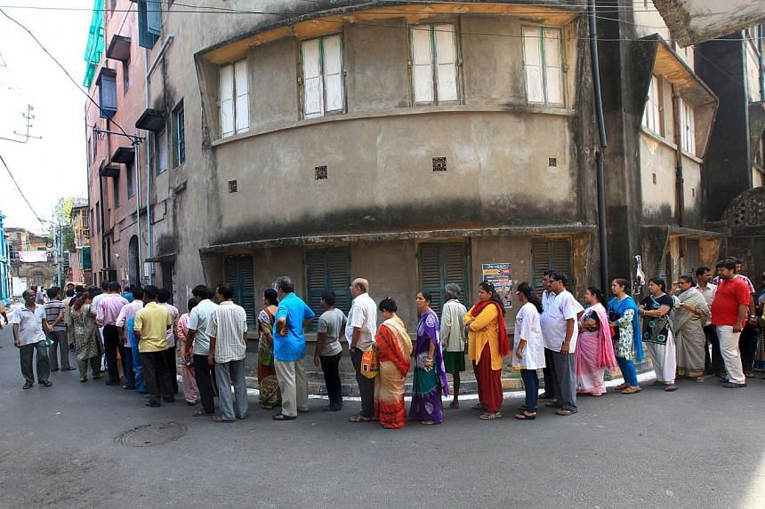 Indian voters wait in line to cast their votes at a polling station during the ninth and final phase of the parliamentary elections in Calcutta, India, on May 12, 2014. -- PHOTO: EPA