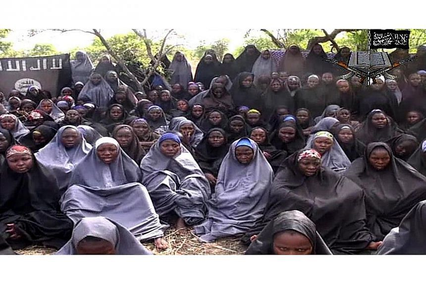 A screengrab taken on May 12, 2014, from a video of Nigerian Islamist extremist group Boko Haram obtained by AFP shows girls, wearing the full-length hijab and praying in an undisclosed rural location. Boko Haram released a new video on claiming to s