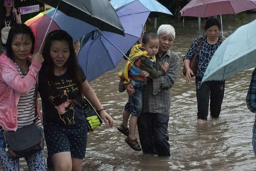 A man carrying a boy walks along a flooded street in Shenzhen, Guangdong province, on May 11, 2014. Three people have been killed and thousands evacuated in several days of rainstorms in southern China, flooding major cities and affecting air and rai