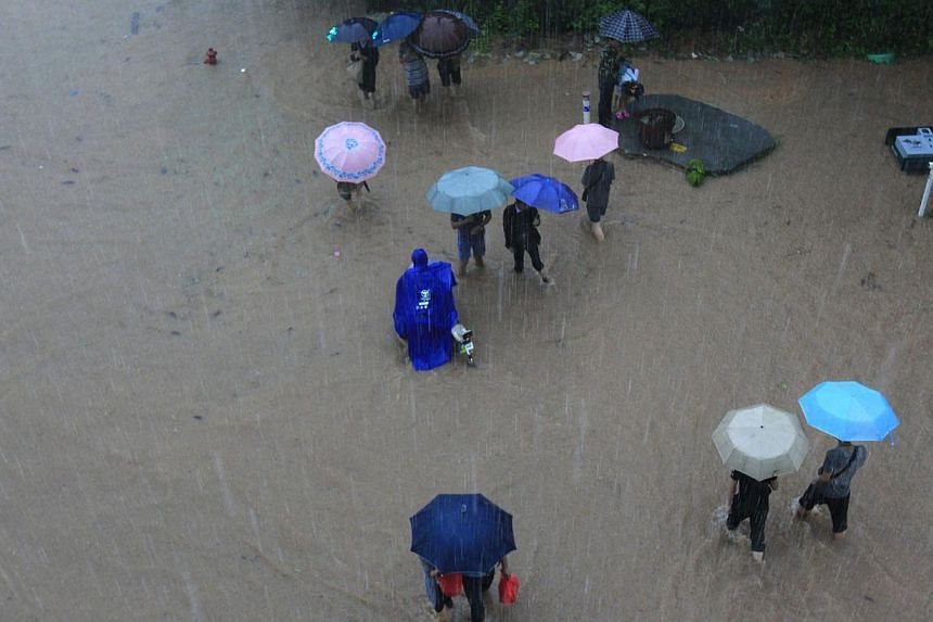 Pedestrians wading through a heavily flooded street in Shenzhen, south China's Guangdong province, on May 11, 2014. -- PHOTO: AFP