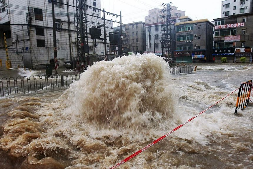 Flood water bursting onto a street from a sewer in Shenzhen, south China's Guangdong province, on May 11, 2014. -- PHOTO: AFP