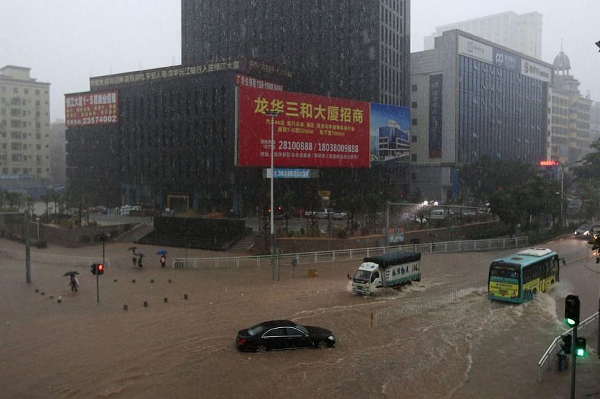 Commuters manoeuvring their way through a heavily flooded street in Shenzhen, south China's Guangdong province, on May 11, 2014. -- PHOTO: AFP