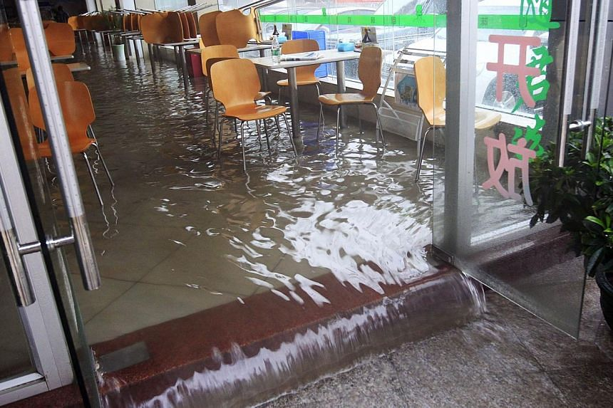 Flood water flowing onto a street from a restaurant in Shenzhen, south China's Guangdong province, on May 11, 2014. -- PHOTO: AFP