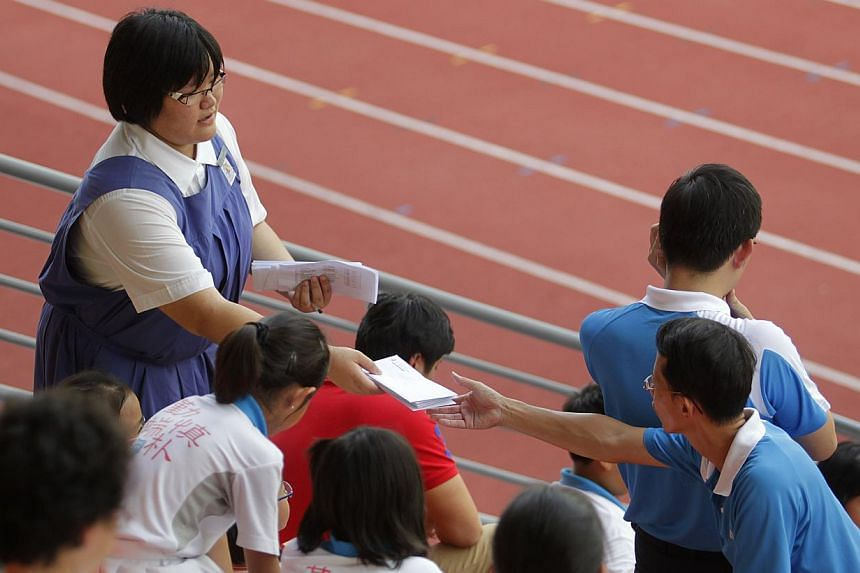 A Secondary School student (left) handing out letters during the national inter-primary school track and field championships held on April 12, 2011, at the Bishan Stadium. -- ST FILE PHOTO:KEVIN LIM