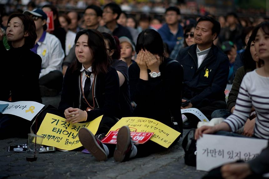 """A woman weeps during a rally paying tribute to victims of the Sewol ferry disaster in Seoul on May 10, 2014. South Korea on May 11, 2014, recognised three people who died saving others in last month's ferry disaster as national """"martyrs"""". -- FILE PHO"""