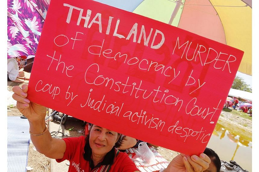 A Thai pro-government Red Shirt protester holds a placard during a rally on the outskirts of Bangkok, Thailand, on May 11, 2014. Six months of political turmoil has created Thailand's biggest ever crisis, the leader of the country's Senate said on Mo
