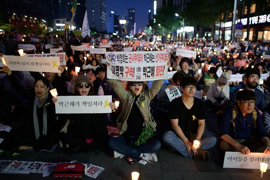 People shout slogans as they hold placards reading 'Your fault, President' and 'down with friends of Lee Myung Bak' during a rally paying tribute to victims of the Sewol ferry disaster in Seoul on May 10, 2014. -- FILE PHOTO: AFP