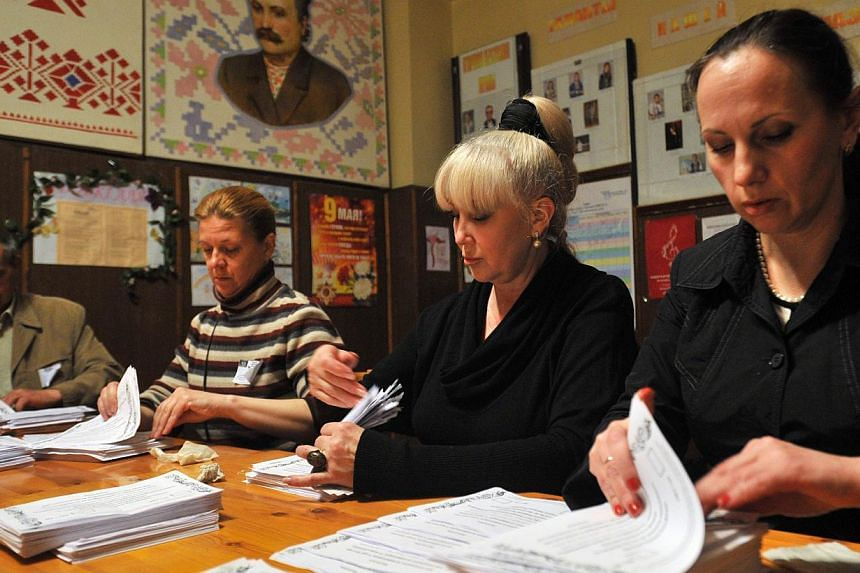Members of an election commission count ballot papers at a polling station in the eastern Ukrainian city of Donetsk on May 11, 2014. -- PHOTO: AFP