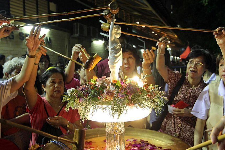 Devotees bathe the Buddha after circumambulating the Hougang stadium on May 10, 2014, each holding a lotus-lamp. -- ST FILE PHOTO: SEAH KWANG PENG