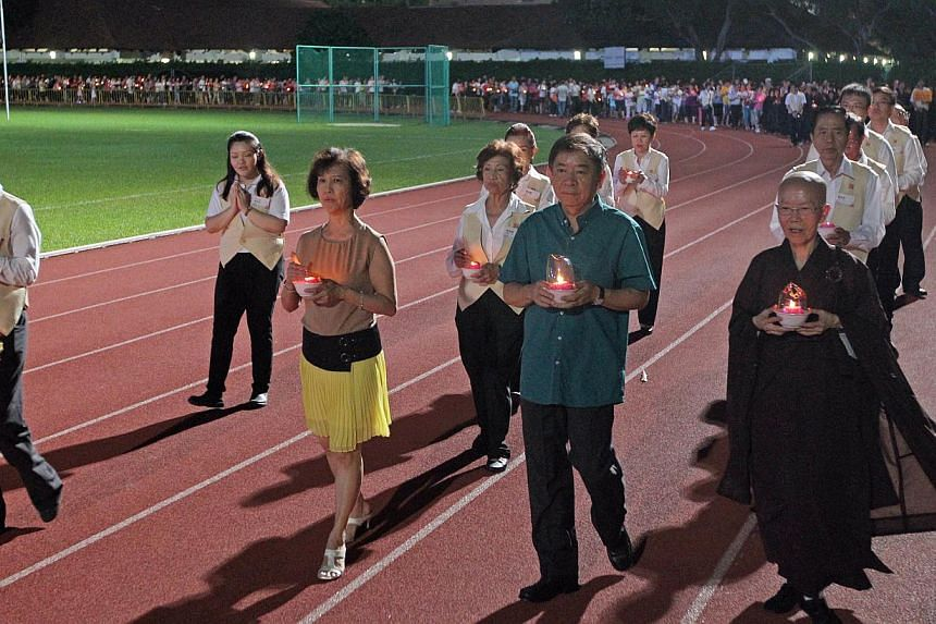 Minister for National Development, Mr Khaw Boon Wan (centre) and Mrs Khaw (left, yellow skirt), Venerable Kuan Yan (right), and thousands of devotees circumambulate the Hougang stadium on May 10, 2014, each holding a lotus-lamp. -- ST FILE PHOTO: SEA