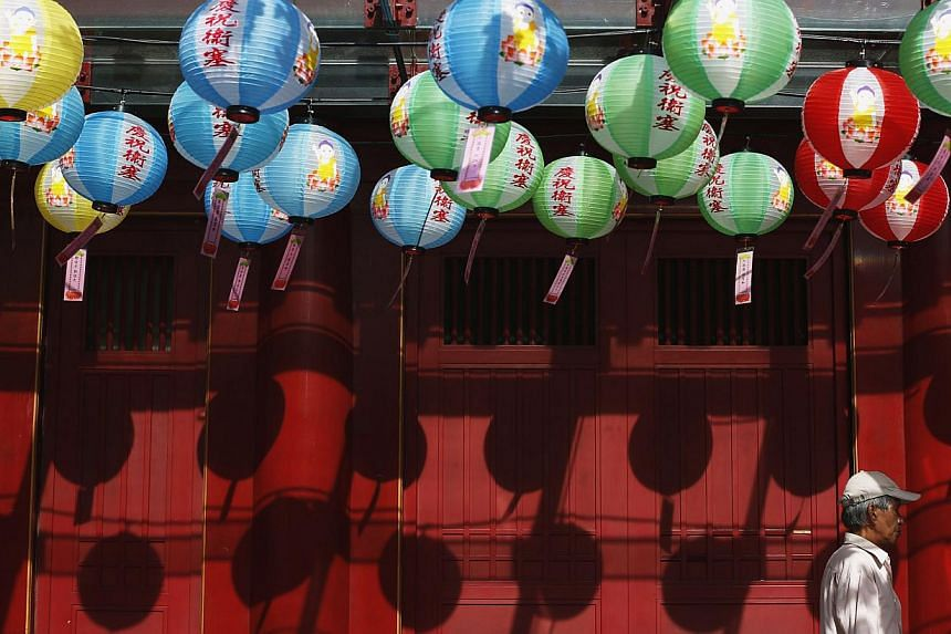 A man passes lanterns carrying well-wishes from devotees outside the Buddha Tooth Relic Temple ahead of Vesak Day in Singapore on May 6, 2014. -- FILE PHOTO: REUTERS