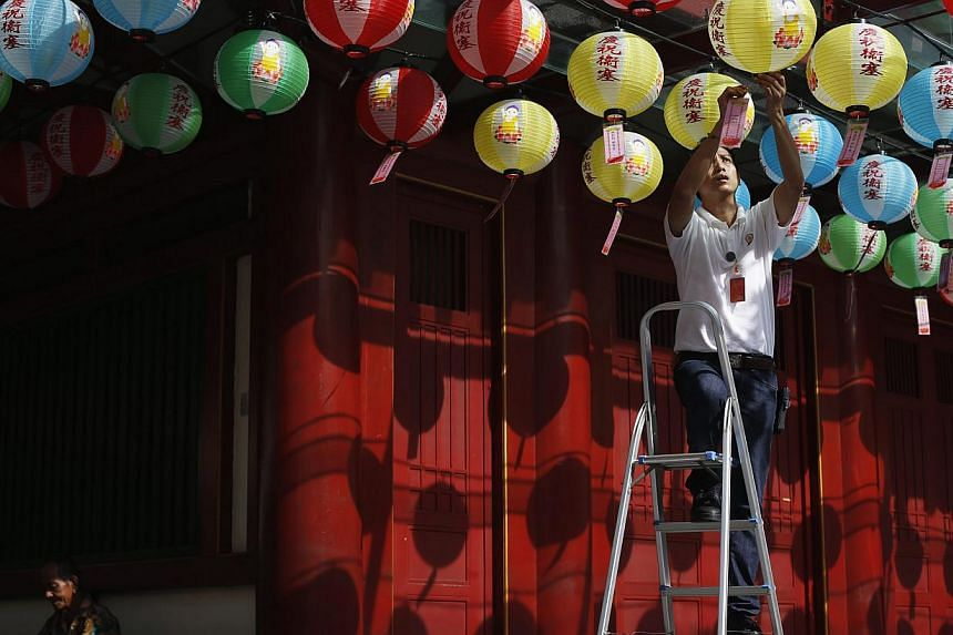 A temple worker hangs well wishes written by donors to lanterns outside the Buddha Tooth Relic Temple ahead of Vesak Day in Singapore on May 6, 2014. -- FILE PHOTO: REUTERS