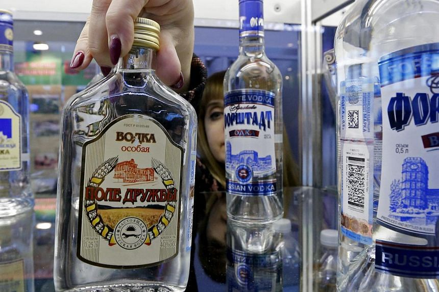 "An employee places a bottle of vodka on a counter during the agro-industrial exhibition ""Agrorus"" in St. Petersburg on April 4, 2014. More than 3 million people died from using alcohol in 2012, for reasons ranging from cancer to violence, the Wo"