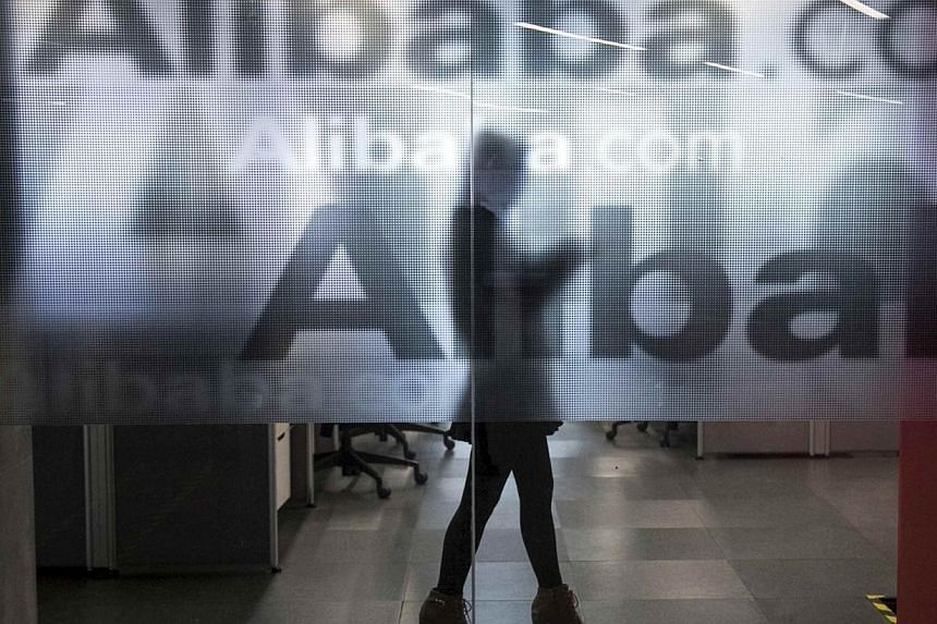 An employee is seen behind a glass wall with the logo of Alibaba at the company's headquarters on the outskirts of Hangzhou, Zhejiang province, April 23, 2014.Mr Jack Ma, the founder and executive chair of Alibaba Group Holding, said investors