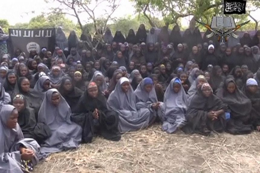 Kidnapped schoolgirls are seen at an unknown location in this still image taken from an undated video released by Nigerian Islamist rebel group Boko Haram. A mother of an abducted Nigerian schoolgirl has identified her daughter in a video posted
