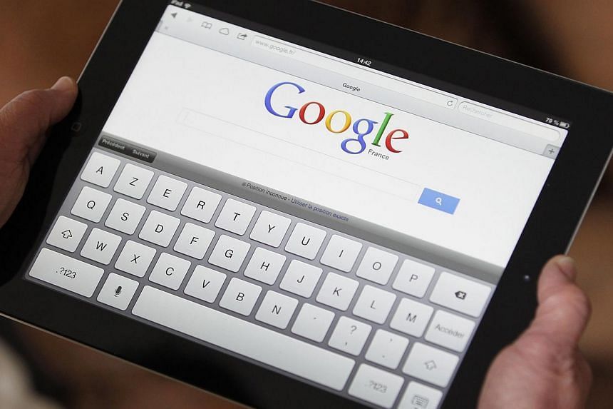 An illustration picture shows a woman holding her Apple Ipad tablet which displays a tactile keyboard under the Google home page in Bordeaux, south-western France, in this Feb 4, 2013, file photo.The EU's top court, in a surprise ruling on Tues