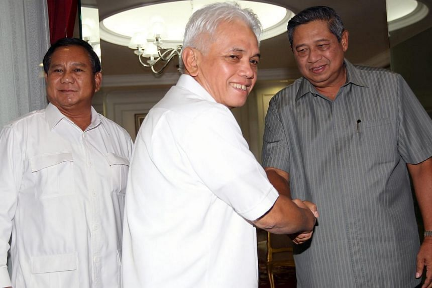 National Mandate Party chairman Hatta Rajasa (centre) shakes hand with Indonesian President Susilo Bambang Yudhoyono (right) accompanied by an Indonesian president candidate and head of the Great Indonesia Movement Party (Gerindra) Prabowo Subianto (