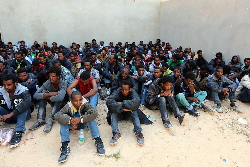 Some of the 340 illegal migrants who were rescued by the Libyan navy off the coast of the western town of Sabratha when their boat began to take on water, sit at a shelter on May 12, 2014 in the coastal town of Zawiya, west of Tripoli.At least