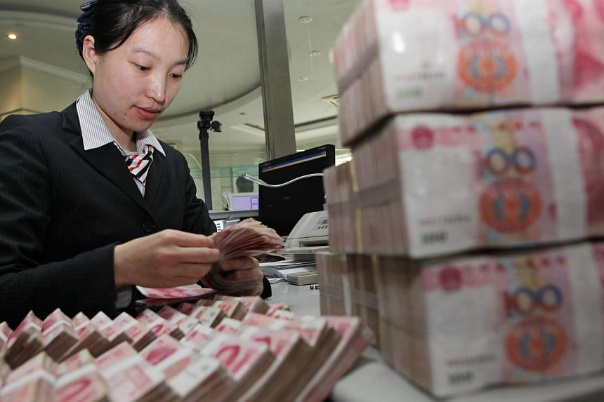 A teller counting notes in a bank in Ganyu county, east China's Jiangsu province. China's yuan will one day compete for a place alongside the mighty dollar as a reserve currency hoarded by central banks, analysts say. -- PHOTO: AFP