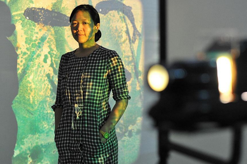 Phi Phi Oanh (above) painted lacquer onto glass slides which are shone through slide projectors for Palimpsest, her first solo show here. -- PHOTO: LIM YAOHUI FOR THE STRAITS TIMES