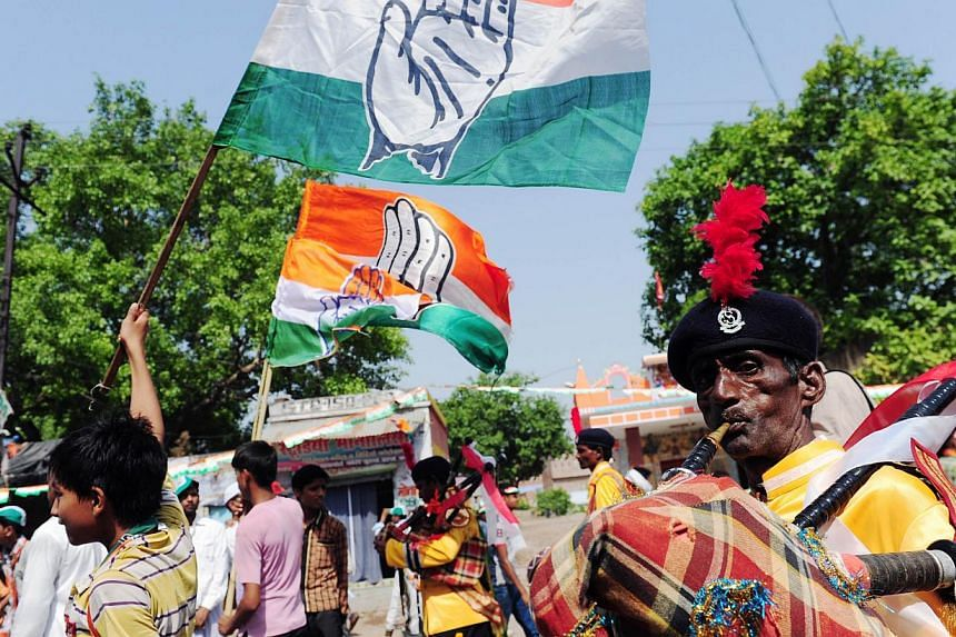 Congress Party members wave flags at a recent rally. The party, which is facing defeat nationwide, has got a face-saving support in two southern Indian states. --PHOTO: AFP