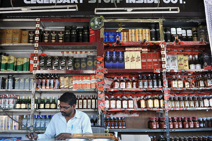 A file photograph of an Indian employee stocking alcohol at a store in Hyderabad. Influencing voters through illicit liquor and cash is an age-old trick across the country, despite heavy penalties prescribed by the Election Commission against vote-bu