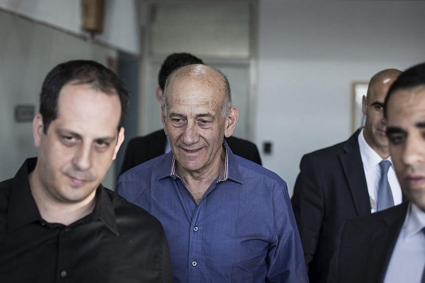Former Israeli Prime Minister Ehud Olmert (centre) arrives at the Tel Aviv District Court on March 31, 2014. Ex-Israeli Prime Minister Ehud Olmert was sentenced to six years' imprisonment on Tuesday for accepting bribes linked to a real estate deal,