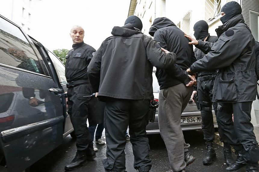 French special Police forces escort a suspect from a residential building in the Meinau suburb of Strasbourg, on May 13, 2014. French anti-terror police on Tuesday arrested six people suspected of going to join jihadist fighters in Syria, the interio