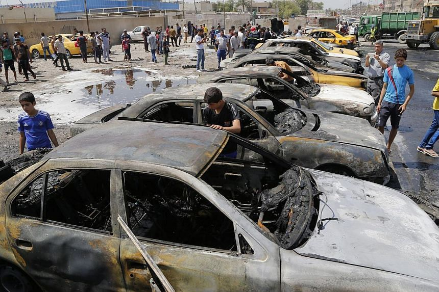 People gather at the site of a car bomb attack in Sadr City district of Baghdad, on May 13, 2014. A spate of rush hour car bombs rocked Shiite-majority areas of Baghdad Tuesday, killing 21 people in the first major series of attacks to hit the Iraqi