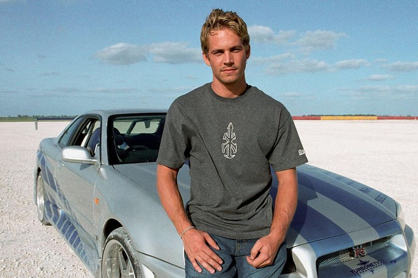 The widow of the man who was driving a sports car when it crashed, killing him and Fast And Furious star Paul Walker last year, is suing Porsche. -- FILE PHOTO:UIP