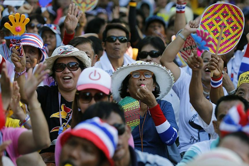 Thai anti-government protesters blow whistles and shout slogans during a rally in front of the Parliament, as the senators meeting inside, in Bangkok, Thailand, on May 12, 2014.Thailand's Senate was due to meet on Tuesday to try to find a solut