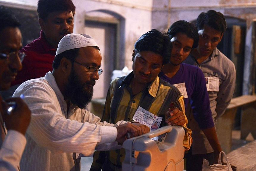 Indian polling station workers take a close look as they seal a box containing an electronic voting machine at the close of polls in the final phase of India's marathon election, in Varanasi on May 12, 2014. A record 551 million voters cast their bal