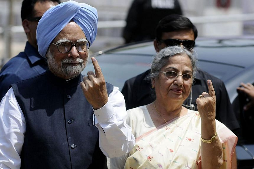 India's Prime Minister Manmohan Singh and his wife Gursharan Kaur show their ink-stained fingers after casting their votes at a polling station during the sixth phase of India's general election in the northeastern Indian city of Guwahati. Saturday w