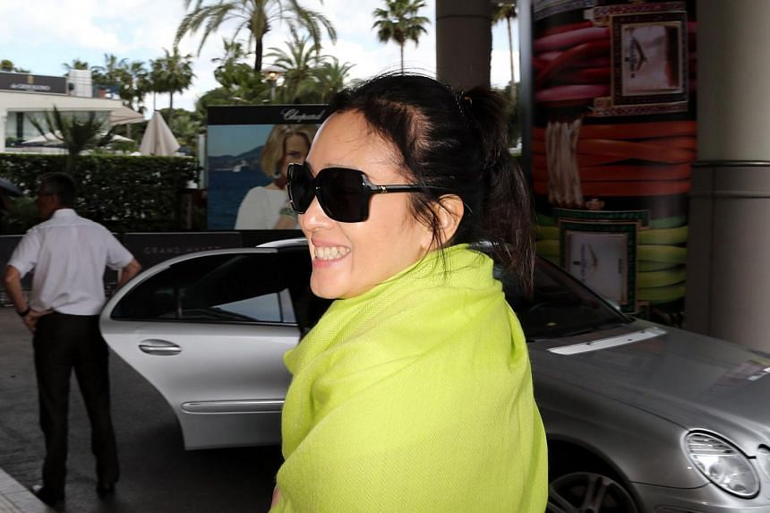 Chinese actress Gong Li smiles as she arrives at the Grand Hyatt Cannes Hotel Martinez on the eve of the 67th edition of the Cannes Film Festival in Cannes, southern France on May 13, 2014. -- PHOTO: AFP
