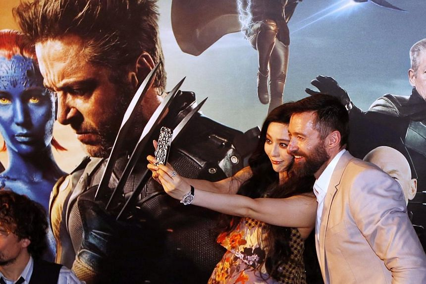 Hugh Jackman and Fan Bingbing take photos while Peter Dinklage (left) wave at fans at the South East Asia premiere of X-Men: Days Of Future Past in Singapore on May 14, 2014. -- PHOTO: REUTERS