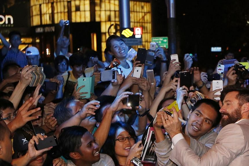 Actor Hugh Jackman takes photos with fans at the South East Asia premiere of X-Men: Days Of Future Past in Singapore on May 14, 2014. -- PHOTO: REUTERS