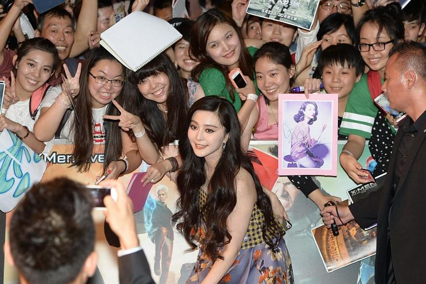 Actress Fan Bingbing poses for photos with fans at the South East Asia premiere of X-Men: Days Of Future Past in Singapore on May 14, 2014. -- ST PHOTO: DESMOND WEE