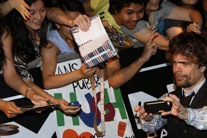 Actor Peter Dinklage poses for photos with fans at the South East Asia premiere of X-Men: Days Of Future Past in Singapore on May 14, 2014. -- PHOTO: REUTERS
