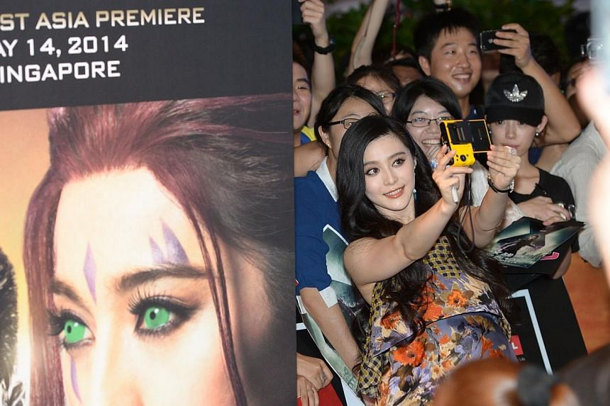 Actress Fan Bingbing poses for photos with fans at the South East Asia premiere of X-Men: Days Of Future Past in Singapore on May 14, 2014.-- ST PHOTO: DESMOND WEE