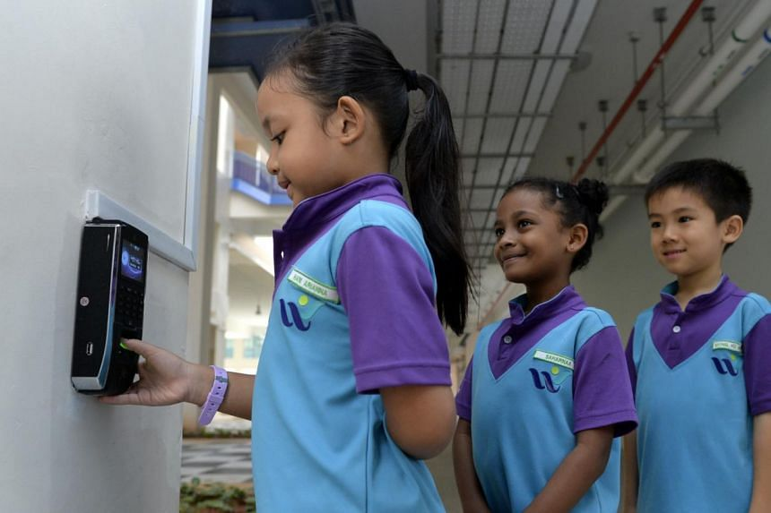 West Spring Primary School pupil Hani Arianna Mohd Hafiz scanning her thumbprint while fellow Primary 1 schoolmates Saharnaa Mahendran and Albert Xiong wait in line.