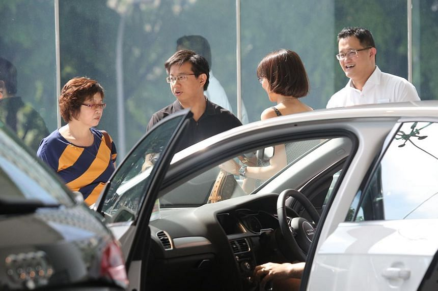 People checking out cars at the Audi showroom in Alexandra Road. Motor traders reported higher showroom traffic and stronger sales over the weekend, and expect the interest to continue this weekend. -- ST PHOTO: ONG WEE JIN