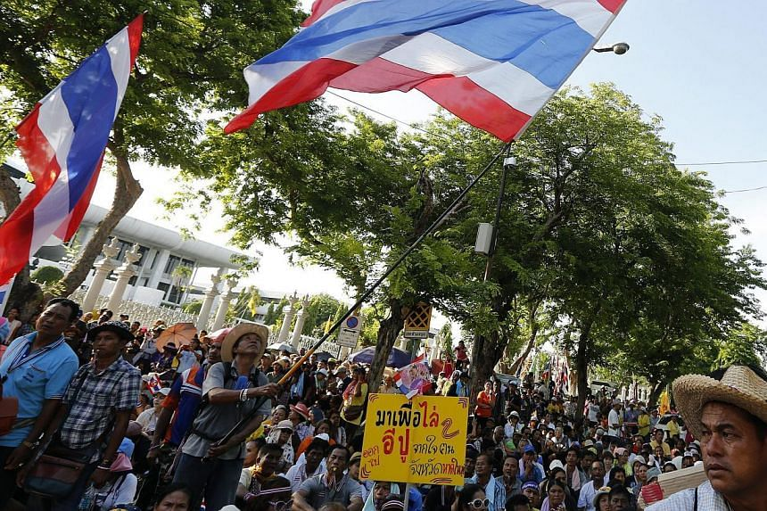 Thai anti-government protesters gather in front of the Parliament, as the senators meet inside, in Bangkok, Thailand on May 12 2014. Thailand's interim prime minister will meet the Election Commission (EC) on Wednesday, in the hope of fixing a date f