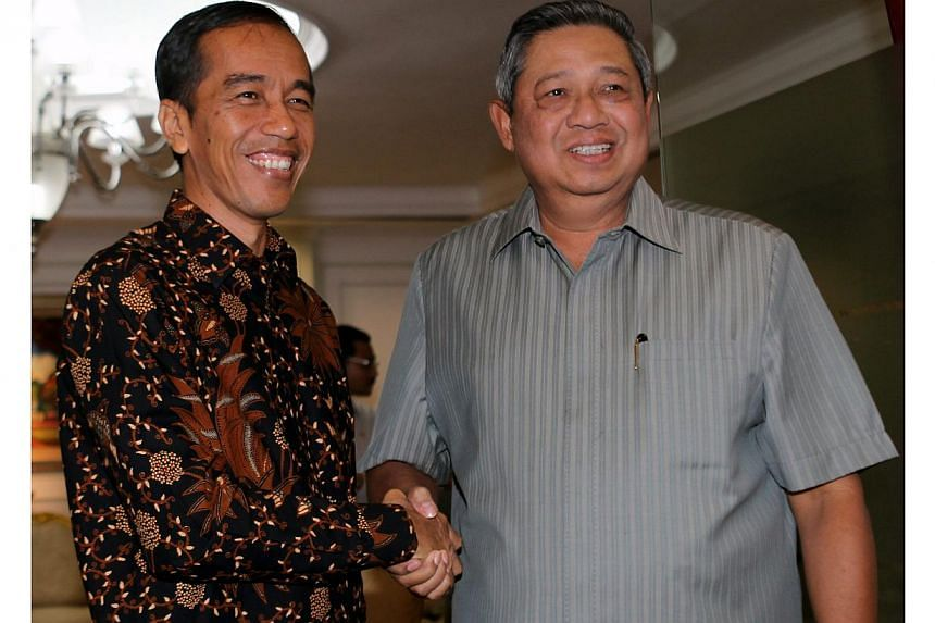 Jakarta Governor Joko 'Jokowi' Widodo (left) an Indonesian presidential candidate nominated by the opposition Indonesian Democratic Party of Struggle, poses with Indonesian President Susilo Bambang Yudhoyono (right) during their meeting in Jakarta, I