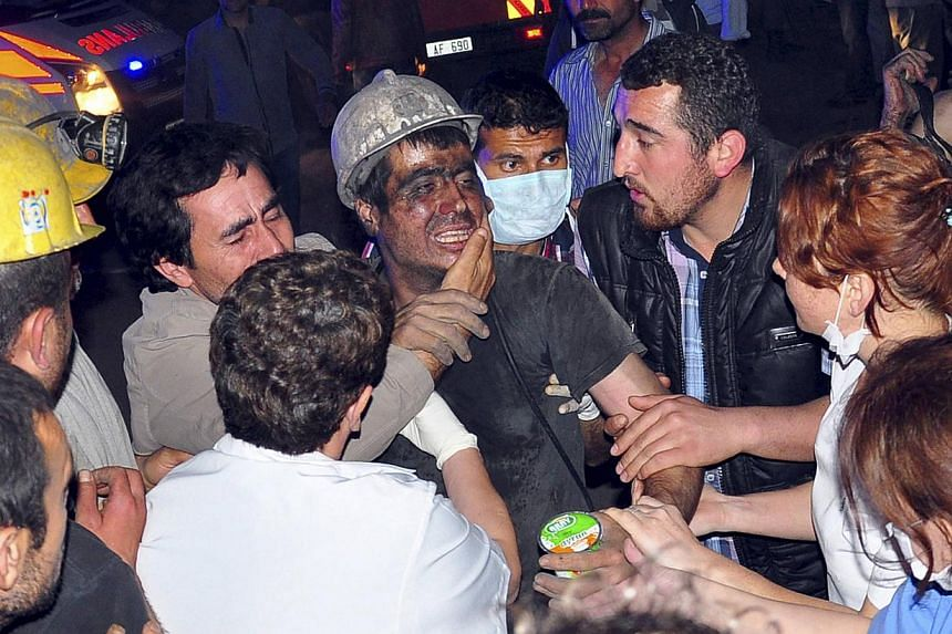 A rescued miner surrounded by relatives, medics and other miners cries after being rescued from a coal mine he was in trapped in Soma, a district in Turkey's western province of Manisa on May 13, 2014. -- PHOTO: REUTERS