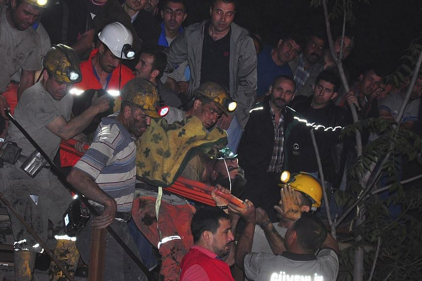 An injured miner is carried to an ambulance after being rescued from a mine where he was trapped in Soma, a district in Turkey's western province of Manisa on May 13, 2014. -- PHOTO: REUTERS